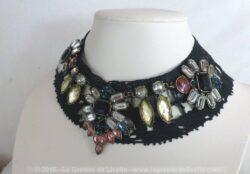 Sur un col en dentelle teinté en noir, des strass multicolores ont été cousus pour un bijoux unique.