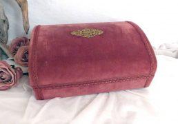 Coffre en velours vieux rose avec décor en laiton sur le couvercle.