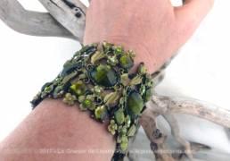 Large bracelet en métal aux belles perles vertes. ce bracelet d'un seul morceau s'écarte pour être mis au poignet.