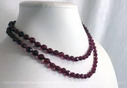Collier ras de cou, sur deux rangs, en perles de verre de couleur carmin ou grenat.