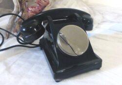 Ancien téléphone en bakélite avec cadran à clapet.