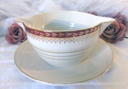 Ancienne saucière en porcelaine opaque aux dessins bordeaux et or.