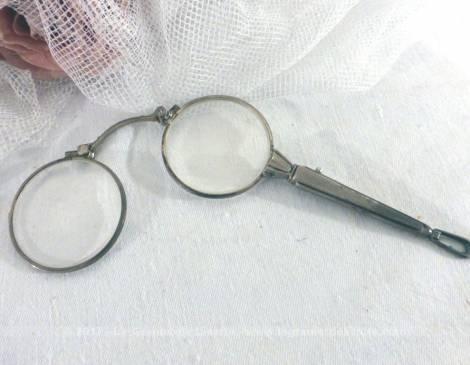 Ancienne paire de lunettes, face à main pliable en métal argenté.