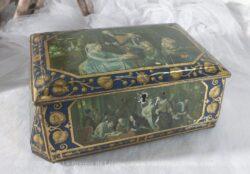 Ancienne boite en métal de forme trapézoïdale avec des sérigraphie de dessins de tableaux.