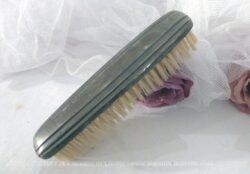 Ancienne brosse à habits en métal argenté.