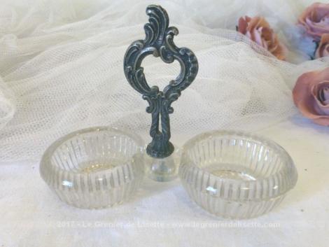 Ancienne salière et poivrière faite de deux compartiments en verre séparés par une décoration en métal.