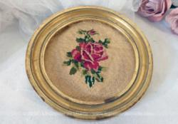 Petit cadre rond, de couleur doré, imitation bois avec une rose brodée.