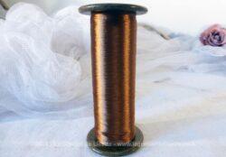 Ancienne grande bobine en carton avec son fil très doux de couleur cuivre.