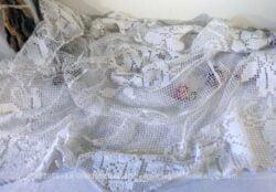 Ancienne nappe carrée de 120 x 120 cm réalisée à la main au crochet en filet avec dessin central de fleurs.