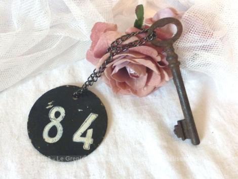 Ancienne clé et sa plaque ronde en fonte avec le numéro 84.