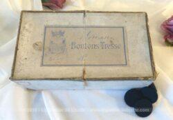 """Ancienne boite de mercerie portant l'inscription """"Boutons Tresse"""" et ses boutons noirs."""