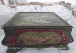Ancienne boite en fer à la forme originale et sérigraphiée d'un dessin représentant un couple de cygnes au bord d'un lac.