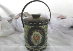 Ancienne boite en fer à la forme originale avec son couvercle et sa anse, sérigraphiée de dessins de fleurs.