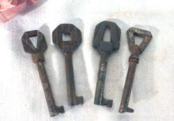 Jeu de 4 anciennes petites clés d'armoire, toutes avec des embouts aux formes géométriques différentes.