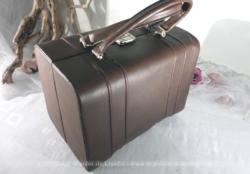 Vanity simili marron vintage avec intérieur entièrement doublé avec nombreuses pochettes.