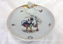 Ancienne assiette chauffante bébé porcelaine en porcelaine de Limoges avec dorures et un modèle de dessin rétro au centre.
