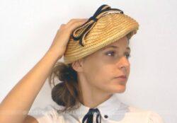 Ancien chapeau en sisal couleur paille avec noeud noir, façon beret ou galette, à la forme asymétrique, avec sur un coté des plis et un joli noeud.