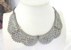 Un collier en métal, patiné de gris sur fond doré, en parfaite imitation d'un ancien col en dentelle.