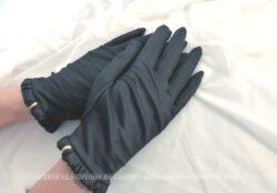 Ancienne paire de gants noirs avec clips dorés . Ils sont en matière extensible satinée noire avec un petit rebord froncé au poignet.