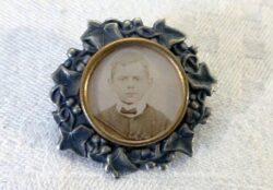 Ancien médaillon en forme de broche aux belles volutes en argent avec à l'intérieur un petit cadre rond au pourtour en laiton et sa photo en sépia.