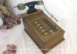 """Ancien standard téléphonique en bois des années 50 de la marque """"Le Téléphone Moderne"""" avec ses boutons et son combiné."""