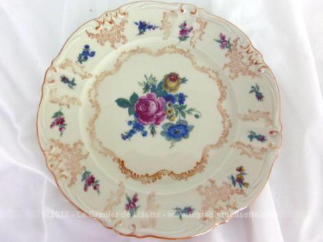 Ancienne petite assiette en porcelaine décorée de volutes dorées et de dessins de fleurs roses avec estampille au dos.
