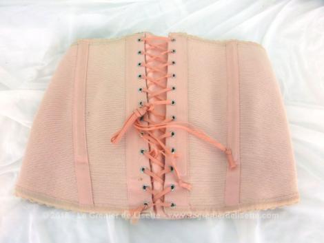 Voici un ancien corset à lacets de couleur saumon. Retrouvé dans une armoire, il est en excellent état, comme neuf, et semble être pour une grande taille.