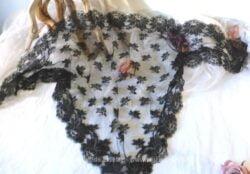 Ancienne mantille en dentelle noire aux petites fleurs avec sa bordure en vague avec de grosses fleurs.
