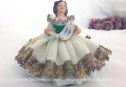 Ancienne petite poupée en biscuit avec jupe toute en dentelle ciselée. Elle est assise sur une chaise et lisant une partition de musique.