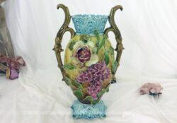 Dans le style Art Nouveau, voici un beau vase en barbotine avec fleurs de lilas en relief. Ses anses, son col et son socle en confirment toute l'harmonie.