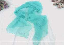 Voici un beau et superbe foulard en crêpe bleu lagon Guy Laroche.
