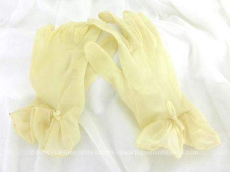 Anciens gants nylon jaunes pales avec noeud datant des années 60/70 avec fronces décorées d'une ganse sur le dessus du poignet.