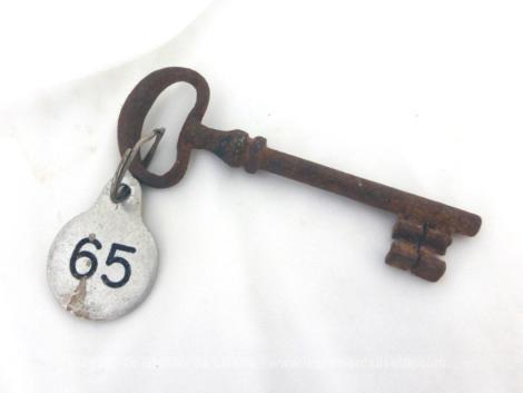 Ancienne clé et sa plaque ronde en métal gravée du numéro 65.