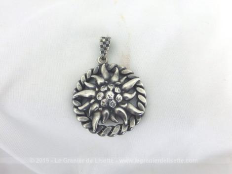Ancienne médaille argent Edelweiss en relief de 3 cm de diamètre avec une torsade comme pourtour et avec le coeur plus ouvragé pour un effet de brillance.