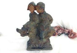 Ancienne statue couple enfants en plâtre polychrome représentant un petit garçon et une petite fille assis sur un rocher.