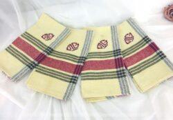 Voici 4 anciennes serviettes torchons monogrammes MG dans un tissus jaune pâle avec quadrillage rouge et marron et les monogrammes brodés en rouge.
