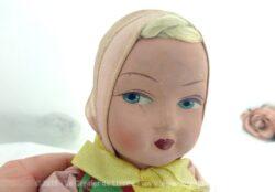 Ancienne poupée en composition et corps tissus rempli de paille dont le visage très bien dessiné nous plonge dans les années 50.