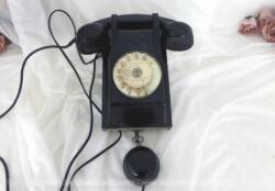 Ancien téléphone bakélite mural avec cadran et son écouteur à suspendre. Sur sa plaque métallique dessous, il porte la mention P et T et la date de 1962.