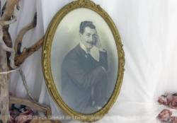 Ancien cadre ovale bois avec homme moustache. Le cadre doré décoré de volutes en relief date du tout début du siècle dernier.