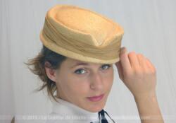 """Ancien chapeau rétro avec ruban années 50, tout en tissus habillé d'un voile tout autour et portant l'étiquette de la modiste """"Paule de Paris""""."""