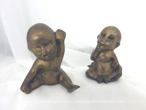 Duo de figurines de bébés en laiton de formes différentes dont le premier est allongé sur le ventre en train de sourire et le deuxième assis avec ses yeux fermés et ronds et un doigt dans la bouche.