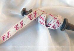 Ancien fuseau à dentelle en bois avec plus d'une mètre d'un ruban vintage avec les lettres TJ brodées en rouge.