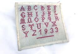 Ancien petit abécédaire daté de 1933 fait main au point de croix en fils rouges, ancien travail ou devoir d'écolière en couture.