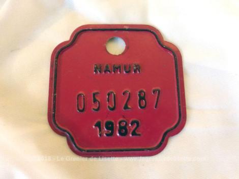 Ancienne plaque vélo belge de 1982 de la ville de Namur en tole laquée rouge et de forme carrée aux coins incurvés.