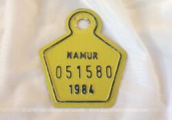 Ancienne plaque vélo belge de 1984 de la ville de Namur en tôle laquée jaune et de forme hexagonale avec un bout arrondi de 8 x 7 cm.