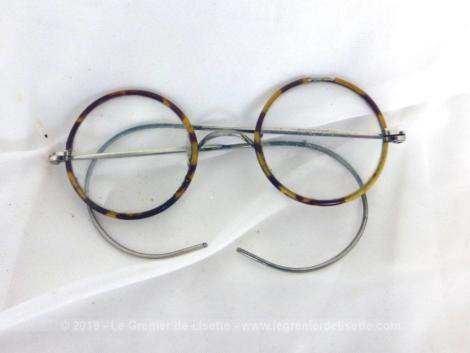 Ancienne paire de lunettes rondes imitation écaille sur une monture en métal avec ses branches très souples avec une maille en spirale.