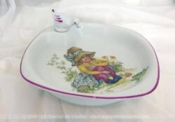 Assiette chauffante bébé porcelaine rétro avec dessin d'une petite fille assise et son bouchon en forme de canard.