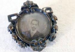 Ancien médaillon avec photo, anciennement une broche, décorée de belles volutes métal argenté avec à l'intérieur un petit cadre rond en laiton scellé et sa photo en sépia.
