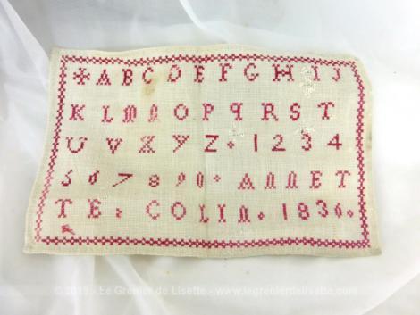 Ancien abécédaire d'écolière de 1836 de 15 x 24 cm, brodé au point de croix en fil rouge avec l'alphabet entier, tous les chiffres et signé de la jeune brodeuse assidue ANNETTE COLIN et l'année 1836.
