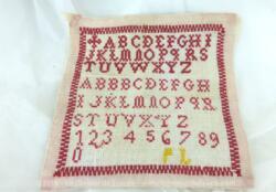 Ancien abécédaire d'écolière de 20 x 19 cm, brodé au point de croix en fil rouge avec deux modèles d'alphabets.